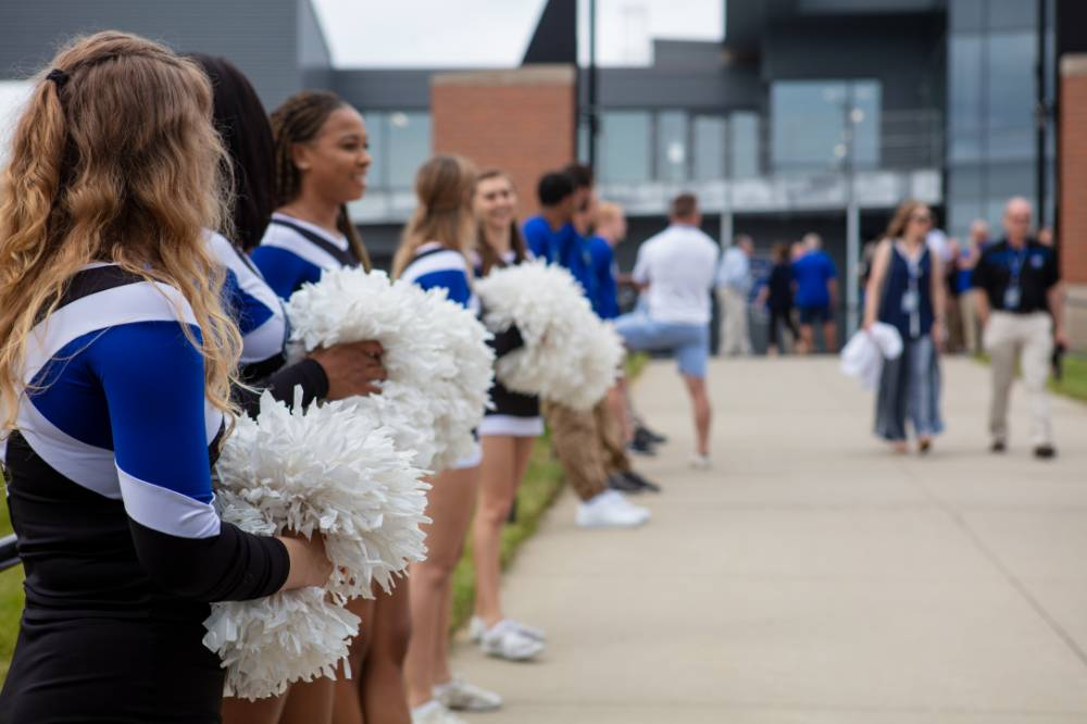 Cheerleaders holding pom poms, standing in a line at the Jamie Hosford Football Center dedication.